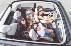4 девушки имея потеху на обратимом автомобиле Стоковая Фотография RF