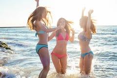 3 девушки имея потеху на пляже Стоковое Фото