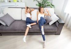 2 девушки имея потеху на софе на живущей комнате Стоковые Фотографии RF