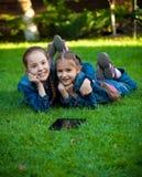 2 девушки имея потеху на траве с таблеткой Стоковые Фото