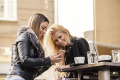 2 девушки имея потеху пока выпивающ кофе Стоковые Фото