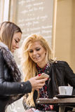2 девушки имея потеху пока выпивающ кофе Стоковая Фотография