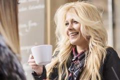 2 девушки имея потеху пока выпивающ кофе Стоковые Изображения