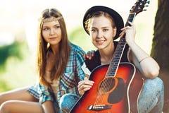 2 девушки имея потеху с гитарой Стоковое фото RF