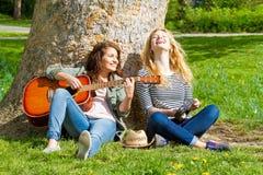 2 девушки имея потеху с ее аппаратурами Стоковое Фото