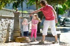 2 девушки имея потеху с фонтаном питьевой воды Стоковая Фотография