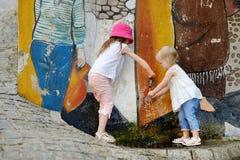2 девушки имея потеху с фонтаном питьевой воды Стоковое Изображение RF