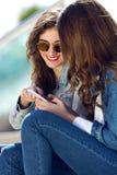 2 девушки имея потеху с smartphones Стоковая Фотография RF