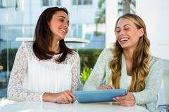2 девушки используют таблетку Стоковая Фотография RF