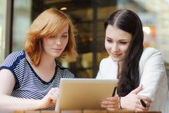 2 девушки используя планшет Стоковое фото RF