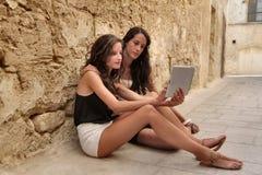 2 девушки используя таблетку Стоковое Фото