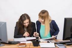2 девушки ищут коллеги сидя совместно правая информация на такой же таблице в офисе Стоковые Фото