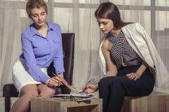 2 девушки ищут решение и рисуют эскизы Стоковое фото RF