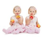 2 девушки идентичного близнца играя с яблоками Стоковые Фотографии RF