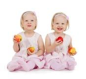 2 девушки идентичного близнца играя с яблоками Стоковая Фотография