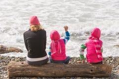 2 девушки и женщина сидя на пляже logon и бросая камнях в воду Стоковые Фотографии RF
