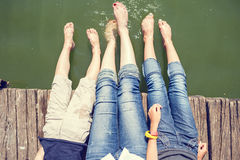 2 девушки и мальчик имеют потеху брызгая ноги в воде Стоковые Изображения RF