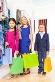 2 девушки и мальчик с красочными хозяйственными сумками Стоковая Фотография RF
