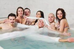 3 девушки и 3 парня имея потеху в бассейне стоковые изображения