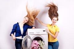 2 девушки и стиральная машина на белой предпосылке Стоковая Фотография RF
