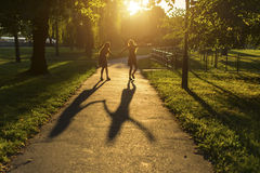 2 девушки идя вниз с переулка держа руки, во время изумительного захода солнца Стоковая Фотография