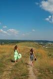 2 девушки идя вниз с холма Стоковые Изображения