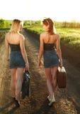 2 девушки идя вдоль дороги на заходе солнца Стоковые Изображения