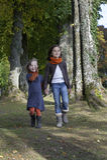 2 девушки идя на путь в древесине Стоковое Изображение