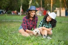 2 девушки идя с его собакой ковбойская шляпа и Стоковая Фотография RF