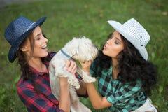 2 девушки идя с его собакой ковбойская шляпа и Стоковые Изображения