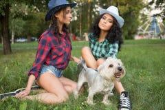 2 девушки идя с его собакой ковбойская шляпа и Стоковые Фото