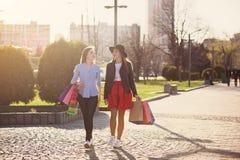2 девушки идя с покупками на улицах города Стоковое Фото