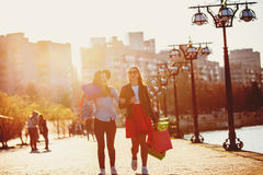 2 девушки идя с покупками на улицах города Стоковые Изображения