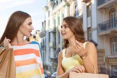 2 девушки идя с хозяйственными сумками Стоковая Фотография