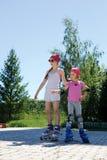 2 девушки катаются на коньках на коньках ролика в парке в лете Стоковые Фото