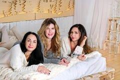 3 девушки кладя на кровать в уютных свитерах Стоковое фото RF