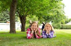 2 девушки кладя на траву Стоковая Фотография RF