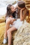 2 девушки маленьких сестры сидя на пляже Стоковая Фотография RF