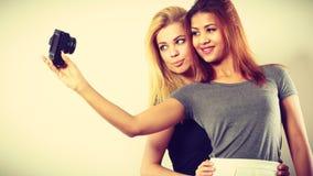 2 девушки моделей фотографируя собственной личности с камерой Стоковая Фотография