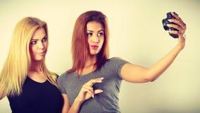 2 девушки моделей фотографируя собственной личности с камерой Стоковое Изображение