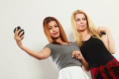 2 девушки моделей фотографируя собственной личности с камерой Стоковые Фото