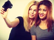 2 девушки моделей фотографируя собственной личности с камерой Стоковые Изображения RF