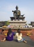 2 девушки моля перед статуей короля Ramkhamhaeng большой в историческом парке Таиланд Стоковое Изображение