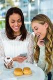 2 девушки наблюдают телефон Стоковые Изображения RF