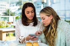 2 девушки наблюдают телефон Стоковая Фотография RF