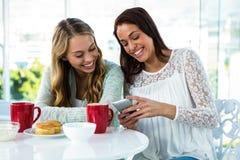 2 девушки наблюдают телефон Стоковые Фото