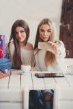 2 девушки наблюдают фото на smartphone Стоковые Фотографии RF