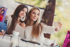 2 девушки наблюдают фото на smartphone Стоковое Фото
