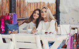 2 девушки наблюдают фото на smartphone Стоковые Изображения