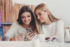 2 девушки наблюдают фото на smartphone Стоковая Фотография
